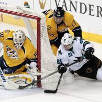 Blocked off: San Jose's Tyler Kennedy shoots on Nashville's Carter Hutton as teammate Nick Spaling defends on Saturday. | AP