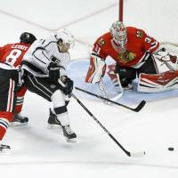 Tag team: Los Angeles' Jordan Nolan moves for his own rebound as Chicago's Nick Leddy (left) and Antti Raata defend on Monday. | AP