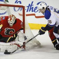 All over it: Calgary goalie Reto Berra defends against St. Louis' Magnus Paajarvi in the first period on Monday night. | AP