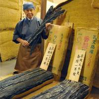 Takashi Okui, president of kelp retailer Okuikaiseido, holds aged kelp in the warehouse of his shop in Tsuruga, Fukui Prefecture, on Oct. 8, 2013. | KYODO
