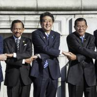 The thin grey line: Prime Minister Shinzo Abe poses in Tokyo on Saturday with (from left) Vietnamese Prime Minister Nguyen Tan Dung, Sultan Hassanal Bolkiah of Brunei, Cambodian Prime Minister Hun Sen and Indonesian President Susilo Bambang Yudhoyono. | POOL