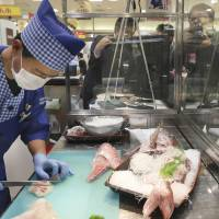 On the menu: Teio Higashino slices a red sea bream for a sashimi plate in front of customers at the flagship Hankyu department store in Umeda, Kita Ward, Osaka, on Thursday. The sashimi was offered for free to around 100 customers to celebrate Japanese cuisine's listing on the UNESCO Intangible Cultural Heritage list. | KYODO