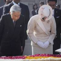 Imperial deference: Emperor Akihito and Empress Michiko pay their respects at the memorial to former Indian leader Mahatma Gandhi in New Delhi on Monday. | AP