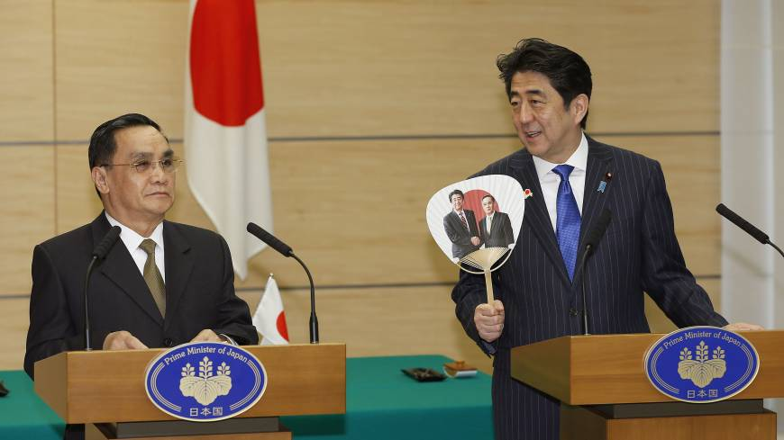 New carrot: Fan in hand, Prime Minister Shinzo Abe shares the stage with Laotian Prime Minister Thongsing Thammavong at a joint news conference at Abe's official residence in Tokyo on Sunday.