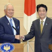 Neighbors: Malaysian Prime Minister Najib Razak and Prime Minister Shinzo Abe hold a joint news conference in Abe's official residence Thursday. | POOL