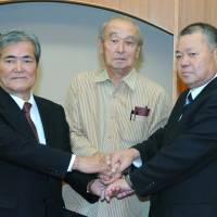 United stand: Former Nago Mayor Yoshikazu Shimabukuro (right) and Bunshin Suematsu (left) shake hands with Okinawa Gov. Hirokazu Nakaima on Thursday in Naha. | POOL