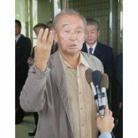 Toeing the line: Okinawa Gov. Hirokazu Nakaima fields questions from reporters on Monday after meeting with Ichita Yamamoto, minister in charge of Okinawa issues, about financial support from Tokyo. | KYODO