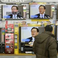 Passing the torch: A man passes by rows of televisions on display airing news broadcasts about the resignation of Tokyo Gov. Naoki Inose on Thursday at a home appliance store in Minato Ward, Tokyo. | KYODO