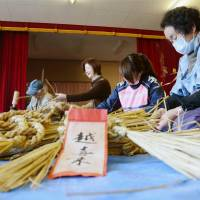 Revival effort: Residents of the disaster-hit Okirai district in the city of Ofunato, Iwate Prefecture, braid local 'shimenawa' on Nov. 23 for use as New Year's ornaments. | KYODO