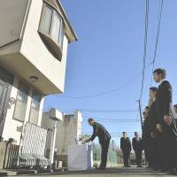 Cold case: Metropolitan Police Department investigators offer prayers Monday outside the home of a family of four slain in December 2000 in their home in Setagaya Ward, Tokyo. The case remains unsolved. | KYODO
