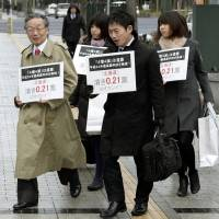 By the numbers: Lawyers head to the Sapporo High Court on Friday with signs showing the disparity in the weight of votes in July's Upper House election. | KYODO