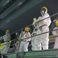 Members of a group of international experts inspect Fukushima No. 1 on Sept. 25. | TOKYO ELECTRIC POWER CO., INTERNATIONAL RESEARCH INSTITUTE FOR NUCLEAR DECOMMISSIONING/AP