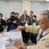 Beyond the Geiger counter: A researcher at Marine Ecology Research Institute in Onjuku, Chiba Prefecture, explains to foreign journalists how a fish sample is prepared for a radiation test. | KAZUAKI NAGATA
