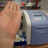 Just a pinprick: A customer performs an easy blood test to check for diabetes at Ayase Pharmacy in Adachi Ward, Tokyo. | MAMI MARUKO