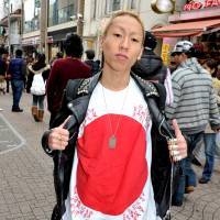 Showing the flag: Daisuke Sumii, 24, a salesman at a Harajuku clothes shop, shows off a T-shirt with the slogan 'This is Japanese rock' while walking through Takeshita-dori. | YOSHIAKI MIURA