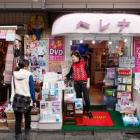 Diversity in action: An ethnic Korean shopkeeper speaks to a potential customer in front of a shop that sells K-pop DVDs and South Korean cosmetics in Tokyo's Shin-Okubo district.  | WASHINGTON POST