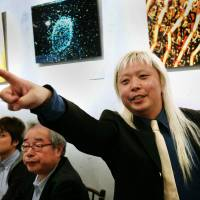 'Rock star' scientist: Physicist Sho Tada explains about elementary particles to people at a cafe in Tokyo's Ginza district recently. | KYODO