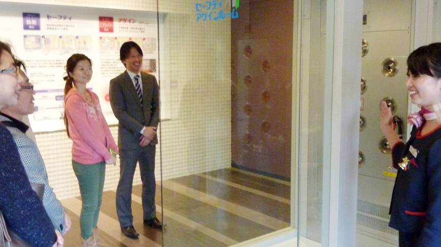 Temporary refuge: An employee of Daiwa House Industry Co. explains about the small emergency rooms installed in each of the firm's new apartment buildings.