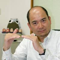 Signs of improvement: Daigo Ishibashi, secretary-general of the Tottori association of organizations for deaf-mutes, responds to interview questions via sign language. | KYODO