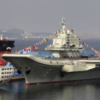 Cause for concern?: China's first aircraft carrier, the Liaoning, is decorated with flags at a shipyard in Dalian in September 2012. | AP