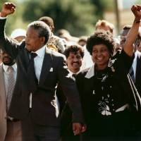 Victorious: Nelson Mandela and his then wife, Winnie Madikizela-Mandela, raise clenched fists as they walk hand-in-hand upon his release from prison in Cape Town on Feb. 11, 1990. | AP