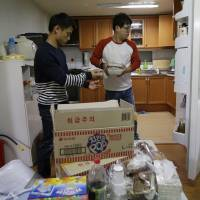 'Bachelor Mom': Kim Tae-hoon (right) puts food in a refrigerator with Hwang Cheol-jin, a North Korean defector, at his home in Seoul on Oct. 28. | AP