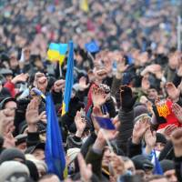 Westward ho!: Protesters wave after U.S. Sen. John McCain addressed a rally in Independence Square in Kiev on Sunday. | AFP-JIJI