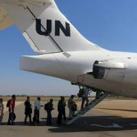 Exit strategy: Noncritical U.N. staffers board a plane in Juba on Sunday to fly to Uganda. | AFP-JIJI