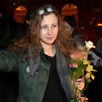 """PR stunt"": Maria Alyokhina of the anti-Kremlin band Pussy Riot is surrounded by journalists and supporters as she arrives in Moscow on Monday after her release from prison. 
