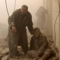 Help close at hand: A Syrian man helps an injured compatriot following an airstrike in Aleppo on Dec. 17. | AFP-JIJI