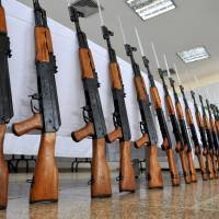 Lined up: A Colombian police officer stands guard next to AK-47 assault rifles seized in Cali, a major center for drug trafficking, in November 2009. | AFP-JIJI