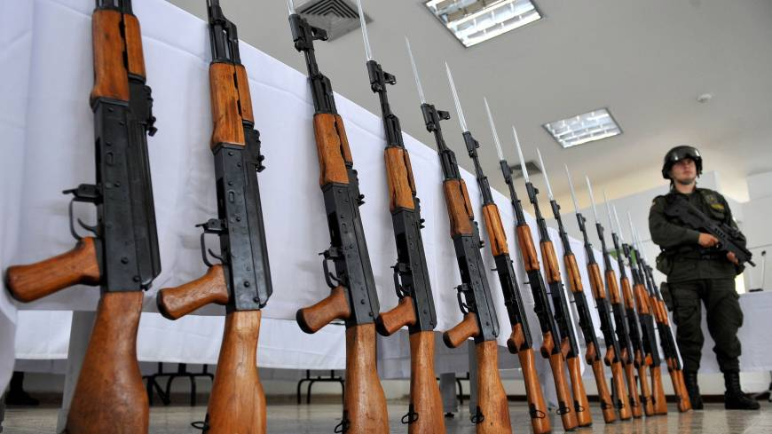 Lined up: A Colombian police officer stands guard next to AK-47 assault rifles seized in Cali, a major center for drug trafficking, in November 2009.