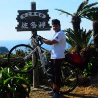 Omar Al-Omair, from Saudi Arabia, poses with his bike at Cape Sata, the southern tip of Kagoshima Prefecture, on Nov. 23, at the end of his cycling journey from the northern tip of the main island of Hokkaido. | OMAR AL-OMAIR