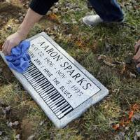 Keeping it clean: Aaron Pritchard wipes off a headstone after laying it on the previously unmarked grave of blues musician Aaron Sparks in Crestwood, Missouri, on Dec. 4. | AP