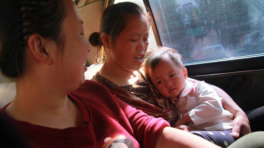 Womb for doubt: Wang Yuan watches as her mother-in-law, Yang Peiyun, comforts her daughter, Beibei, in a taxi in Zhuzhou, China. Beibei is more comfortable with her grandmother, who has raised her since she was 9 months old.