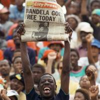 Prisoner no more: A man holds up a newspaper announcing the release of Nelson Mandela at a rally Feb. 11, 1990, in Soweto, South Africa. | AFP-JIJI