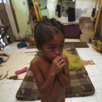 Little to cheer: Typhoon survivor Gabriel, 5, shivers at a temporary shelter in Tacloban, the central Philippines, on Sunday. | AP