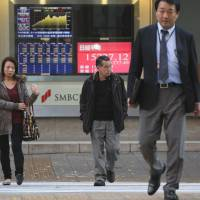 Frothy again?: Pedestrians walk in front of a monitor displaying the closing figure of the Nikkei average outside a securities firm in Tokyo last month. | BLOOMBERG
