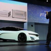 Independent thinking: Tetsuo Iwamura, executive vice president of Honda Motor Co. and president of American Honda Motor Co., speaks on stage next to the automaker's FCEV concept vehicle at the LA Auto Show in Los Angeles on Nov. 20. | BLOOMBERG
