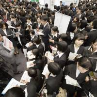 In the hunt: University students crowd the floor of a job fair in Shibuya Ward, Tokyo, on Sunday, the start of the official job recruitment season for March 2015 graduates. | KYODO