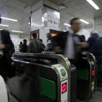 Pay as you go: People pass through ticket gates at a Tokyo train station on Nov. 13. | BLOOMBERG