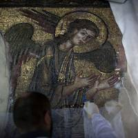 Handle with care: A restoration expert works on a mosaic in the Church of the Nativity in the West Bank city of Bethlehem. | AP