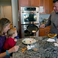 Scrambled: Dave Barzetti, his wife, Carla, and daughter, Grace, have breakfast at their Newtown, Connecticut, home on Nov. 23. Dave, a welder and target shooter, says the debate in the town over guns reflects troubling changes. | AP