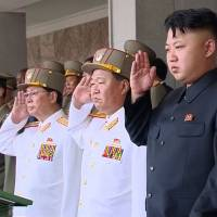 Special event: North Korean leader Kim Jong Un and Jang Song Thaek (third from right), the former vice chairman of the National Defense Commission, salute during a parade in Pyongyang in July. | AP