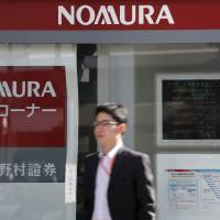 On the outside: A man passes a Nomura Securities Co. branch in Tokyo in October. | BLOOMBERG