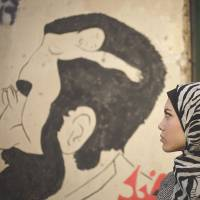 Throwing down a challenge: Egyptian rapper Myam Mahmoud stands next to a mural in downtown Cairo on Dec. 10. | AP