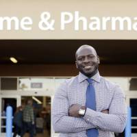 In the money: James Lott stands outside the Wal-Mart store where he works as a pharmacist in Bonney Lake, Washington, on Nov. 21. Lott, who lives in nearby Renton, adds significantly to his six-figure salary by day-trading stocks, making him part of America's 'new rich.' | AP