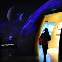 Rising star: A girl visits an astronomy museum in Beijing on Wednesday. With Asian nations' successes in space this year, the established space powers are concerned that a dangerous intra-Asian rivalry in space could lie ahead. | AFP-JIJI
