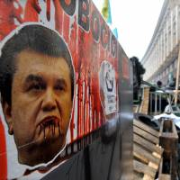 Persona non grata: People walk past a portrait mocking Ukrainian President Viktor Yanukovych in Kiev on Monday. | AFP-JIJI