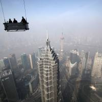 Thriving metropolis: Workers on a suspended platform prepare to clean the Shanghai World Financial Center on Jan. 30. The number of urban dwellers will nearly double over the next 30 to 40 years, a U.N. agency forecast Monday. | BLOOMBERG